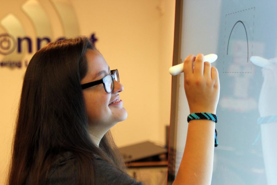 Sophomore Reyna Kendrick draws on one of the two Jamboards now available for students and teachers in the learning commons.