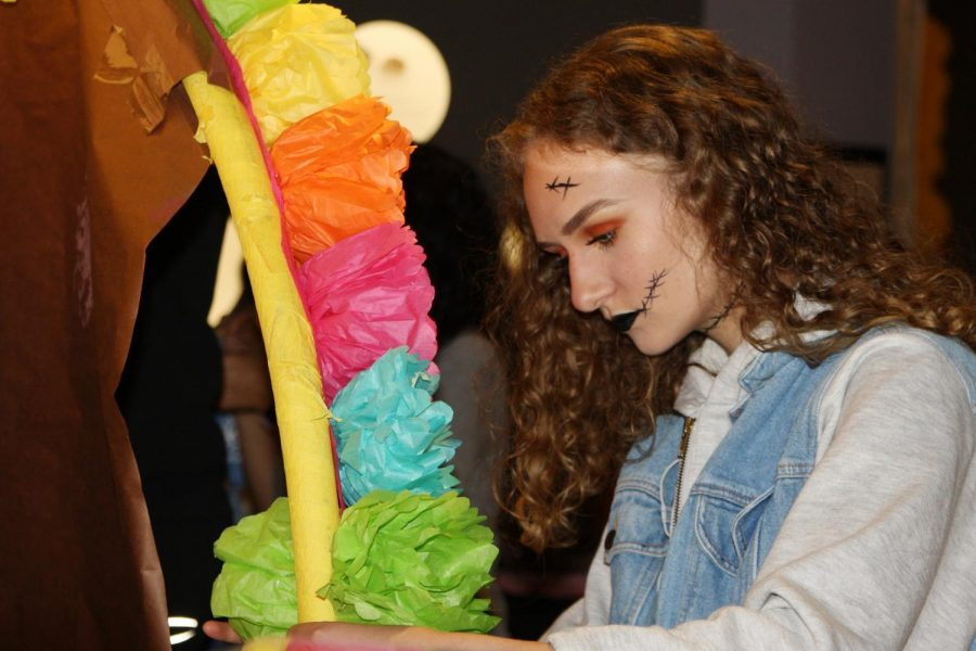 Junior and Spanish IV student Madeline Shadduck glues flowers she made in class on the arch of the ofrenda while setting up at the museum.