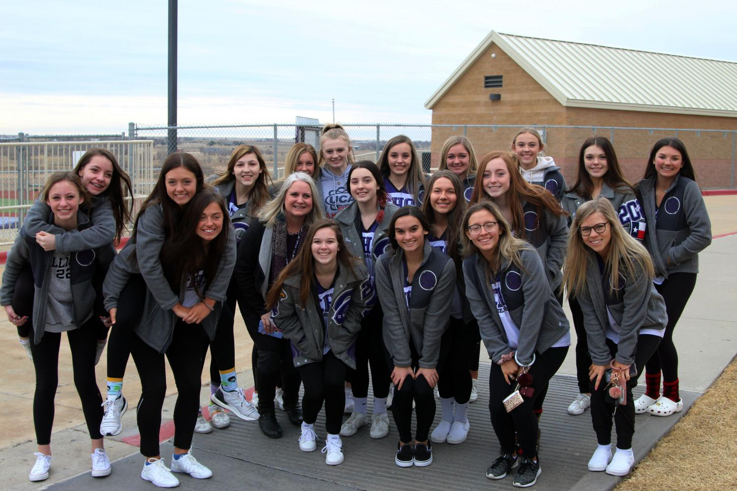 Principal Jennifer Boren accompanies the varsity cheerleaders before the team leaves for state competition following a school-wide send-off.