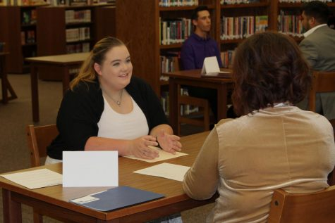 Senior Harley Tidwell interviews with a community member during Interview Week.