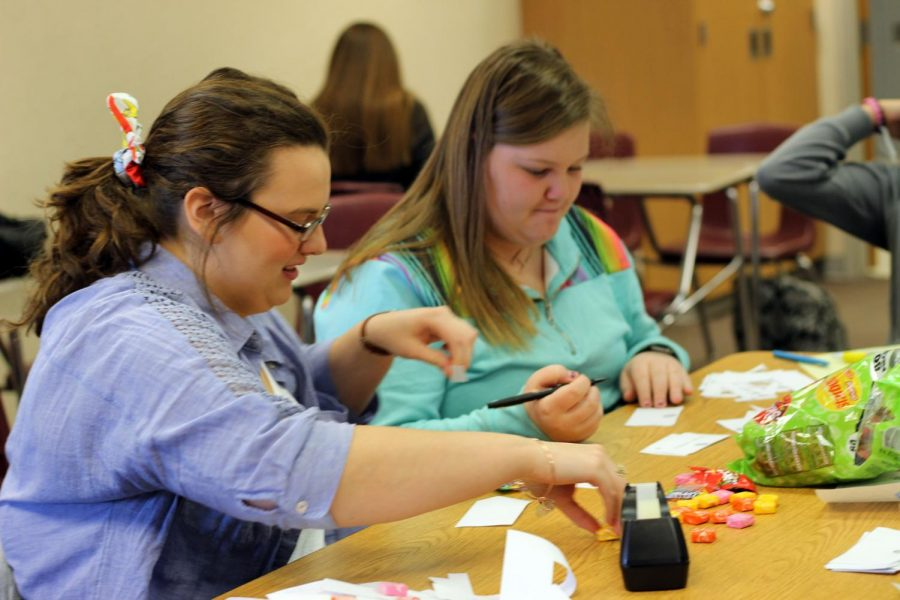 Senior Hannah Winbolt and freshman Huston Smith tape candy to affirmation candy grams at a Leo Club meeting Tuesday, Feb. 25.