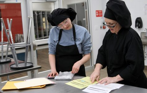 Senior Rebekah Higgins and her culinary arts teacher Carrie-Anne Stanglin discuss Higgins' ballots from the Cupcake Battle competition.