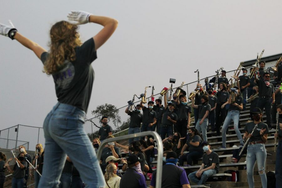 Junior drum major Abigail Bell leads the band during a school chant.