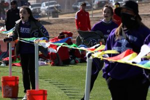 Junior Breanna Stuart and freshman Hannah Stuart cheer for and time their brother, freshman Anthony, at a track meet.