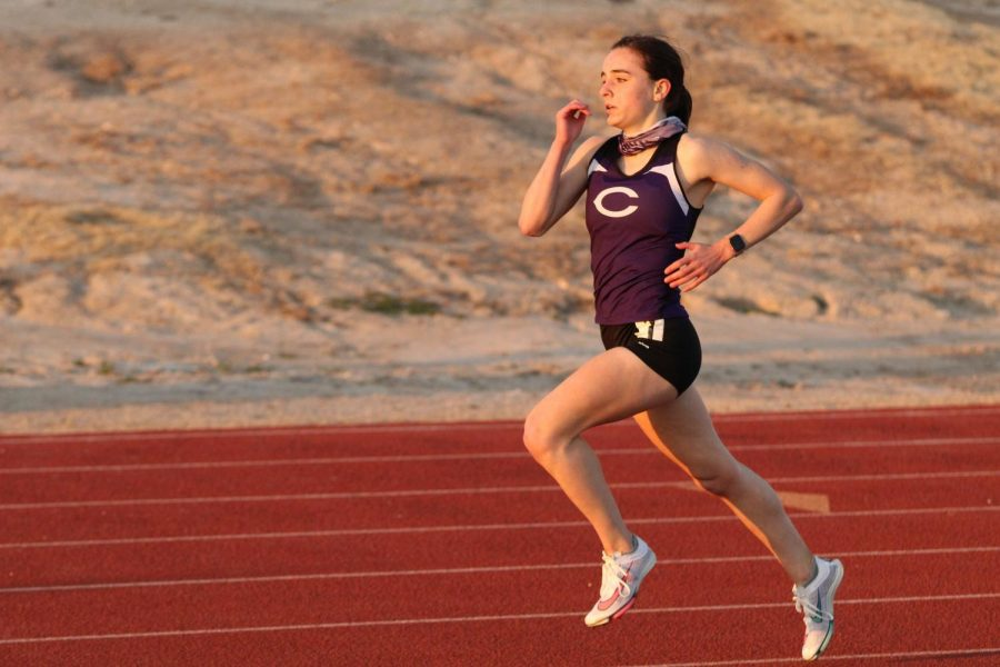 """Junior Breanna Stuart runs the 3200 meter during a March track meet. """"I have been running the one and two mile primarily throughout high school, and I want to push myself as much as possible,"""" Stewart said. """"Our team this year has been pretty good. Everyone has been competitive and giving it their all in order to score points for the team."""