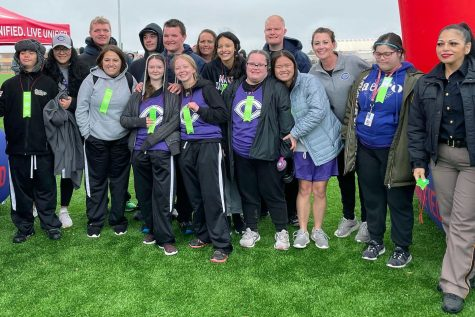 "Before competing at regionals, the team gathers together in the rain. Senior Chloe Fierro said the track meet was fun. ""I did long jump,"" Fierro said. ""We worked really hard to get here. I"